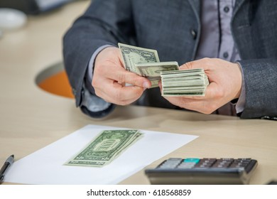 A young businessman is counting a big amount of money in his hands.
