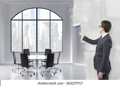 Young businessman covering a picture of a meeting room for six people in New York with grey paint using a roller. Concept of reorganization.