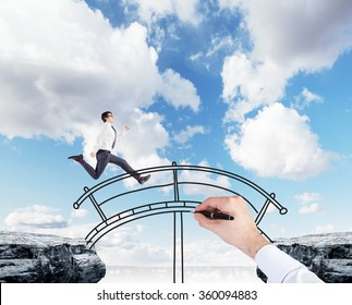 A young businessman crossing the drawn bridge between two cliffs, hand drawing the bridge, blue sky at the background. A concept of bridging the gap.