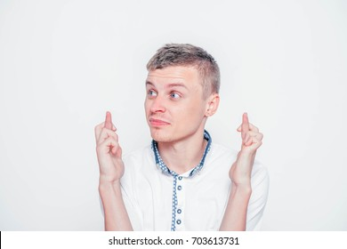 A young businessman crossing his fingers in hope, isolated on white background