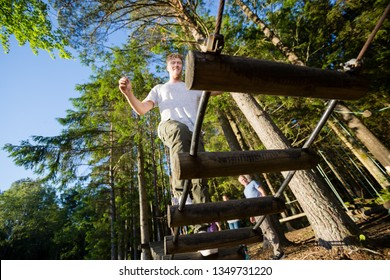 Young Businessman Crossing Log Bridge In Forest