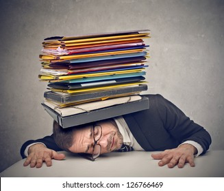 young businessman crushed by folders work