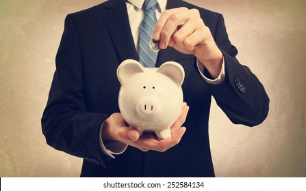Young businessman depositing money in piggy bank