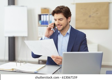 Young businessman discussing a handheld document on a mobile phone with a pleased smile while seated at his desk in the office