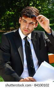 young businessman with documents sitting in the park and looking at someone