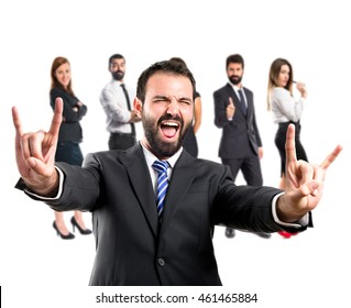 Young businessman doing the horn sign with many people behind
