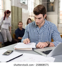 Young businessman doing paperwork at his desk in the office in front of a laptop as his colleages work in the background