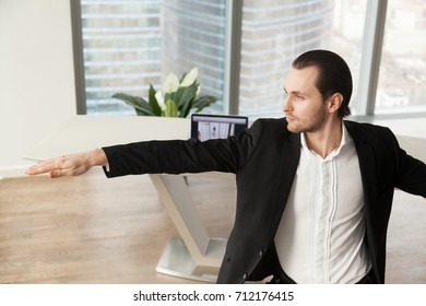 Young businessman doing yoga at workplace in warrior pose. Calm businessman meditating in modern office setting. Reducing discomfort at workplace, staying in focus, relieving stress at work concept.