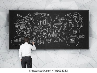 Young businessman drawing business icons on blackboard. Back view. Concept of starting business.