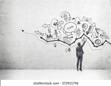young businessman drawing many different business icons on a concrete wall over a graph. Back view. Concept of business development.