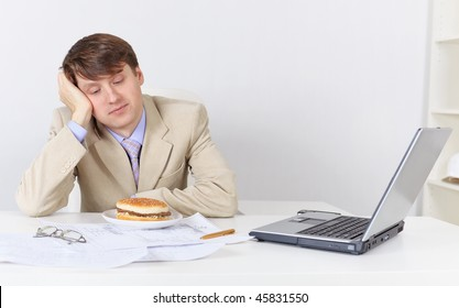 Young businessman, dreamily looking at the sandwich