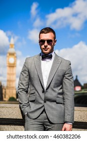 young businessman dressed in a suit, tie and glasses stands on a background of Big Ben