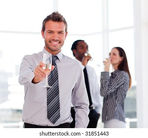 Young businessman drinking champagne and celebrating a success