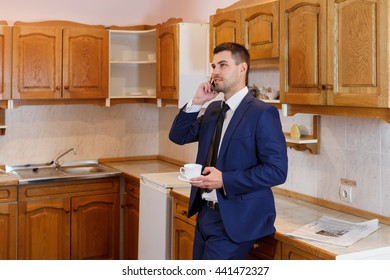 Young businessman drinking coffee and talking on the phone