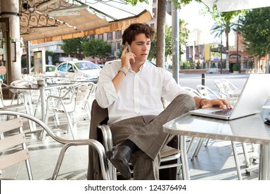 Young businessman drinking a cup of coffee while sitting at a coffee shop terrace table using a laptop computer and making a phone call on his smart phone, outdoors.