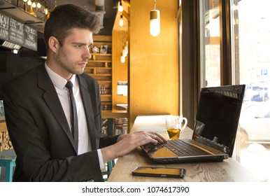 young businessman drinks tea and uses laptop, in cafe
