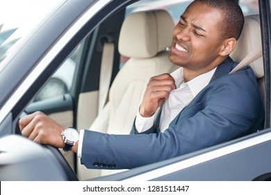 Young businessman driver sitting inside the car driving holding collar aside feeling hot uncomfortable side view in opened window close-up