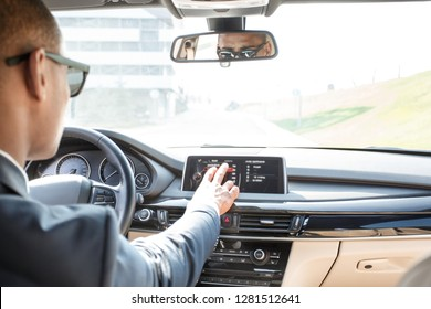Young businessman driver wearing sunglasses sitting inside the car driving choosing destination on navigator panel view from the back seat
