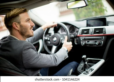 Young businessman driving in the modern car