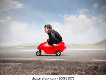 Young businessman driving a toy car on a road