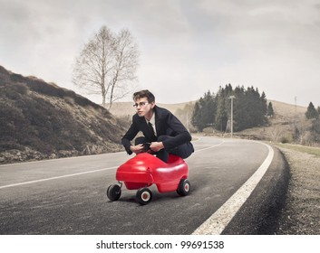 Young businessman driving a toy car on a country road