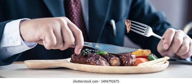 young businessman eating rib steak on wooden tray at restaurant