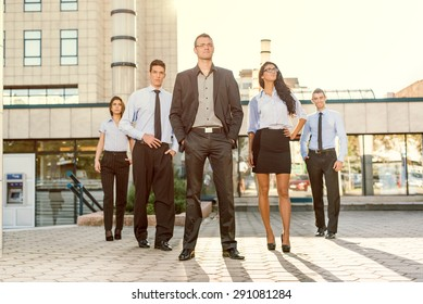 Young businessman, elegantly dressed with his hands in his pockets, standing proudly with his team of young businesswomen and businessmen in front of office building illuminated backlit sun.