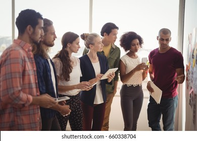 Young businessman explaining to creative team standing at office