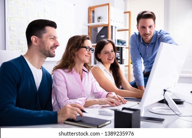 Young Businessman Explaining Plan To Colleagues On Compute At Workplace