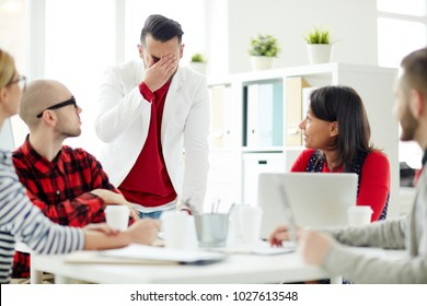 Young businessman expressing confusion in front of his colleagues during working meeting