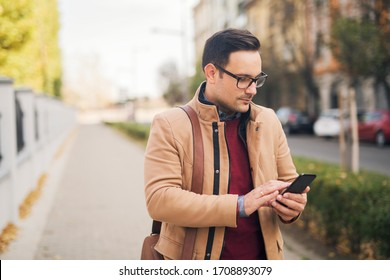 Young businessman with eyeglasses standing on the street and typing a message on his phone.