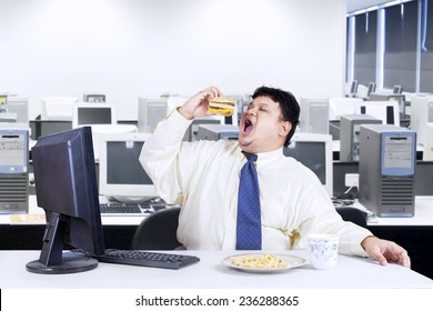 Young businessman with fat body working in the office while eating junk food