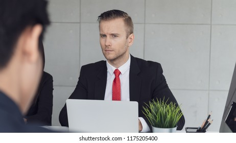 Young businessman feeling suspect in his colleague or partner while working in office or meeting in meeting room.