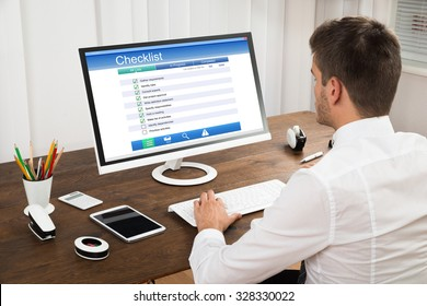 Young Businessman Filling Checklist Form On Computer At Wooden Desk