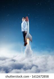 Joven hombre de negocios volando sobre las nubes con un cohete. Iniciar el concepto de negocio.