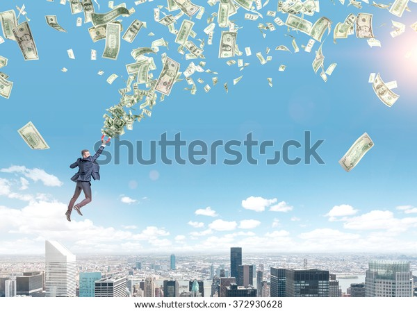 young businessman flying over Paris with a magnet in hand that is pulled to money tornado. Paris and blue sky at the background. Concept of strivig for wealth.