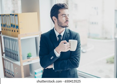 Young businessman is focused, he looks in the window while drinking coffee in office. He is in formal wear