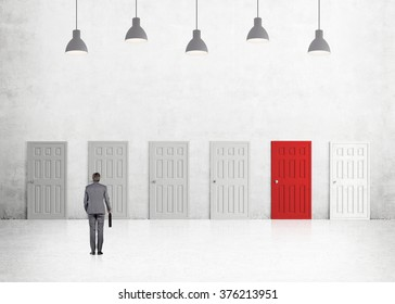 A young businessman with a folder standing in a room with numerous closed doors, one of them is red. Five lamps above. Back view. Concrete background. Concept of finding a way out.