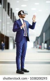 Young businessman in formalwear and vr headset standing inside modern building and touching virtual display