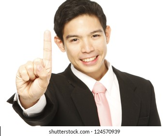 A young businessman gesturing number one with his hand. Shallow depth of field focusing on the hand.