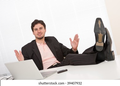 Young businessman gesturing at office having legs up