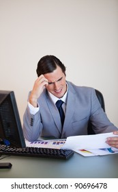 Young businessman getting a headache from looking at paperwork