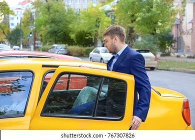 Young businessman getting into taxi car