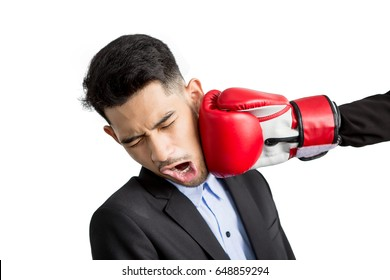 Young businessman getting punch in his face with red boxing gloves on white background. Business competition concept
