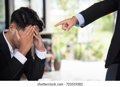 Young businessman getting stressed by his boss at the meeting