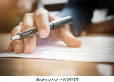 Young businessman gives pen and documents agreement with customer to sign contract. Concept agreement