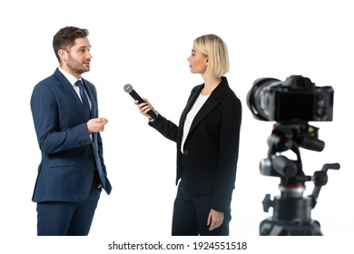 young businessman giving interview to blonde journalist with microphone near digital camera on blurred foreground isolated on white