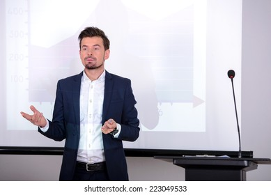 Young businessman giving presentation to his colleagues