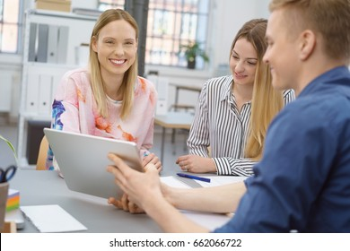 Young businessman giving a presentation to two female colleagues showing them the screen of his tablet pc as the sit around an office table