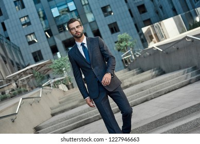 Young businessman with glasses and a beard descends the stairs